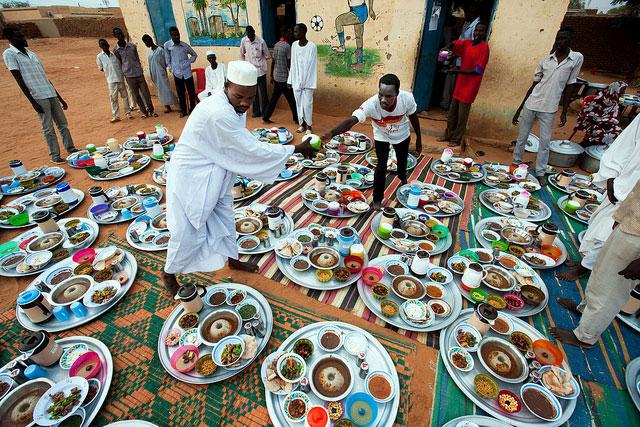 Due uomini preparano vassoi di cibo nella scuola Al Tijane a El Fasher per l'iftar, pasto serale che spezza il digiuno mussulmano nel mese del ramadan.
