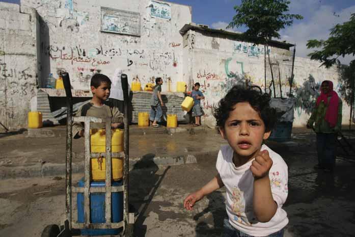 """Foto di due bambini che giocano con delle taniche gialle a Gaza, nei Territori Occupati Palestinesi. Foto tratta dal rapporto della Croce Rossa """"GAZA 1.5 million people trapped in despair""""."""