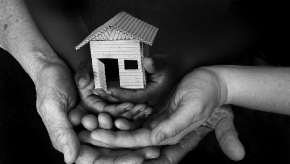 Black and white photo - an adult and child's hands holding a small house made of cardboard