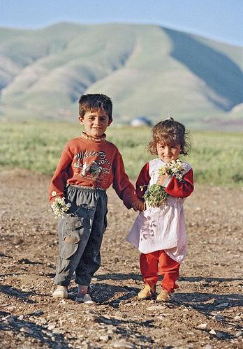 Bambini iracheni in un campo di sfollati interni con dei fiori in mano, Iraq, 1997