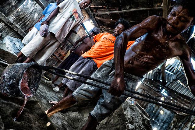 Lavoratori in una fabbrica metallurgica versano un composto liquido in una forma