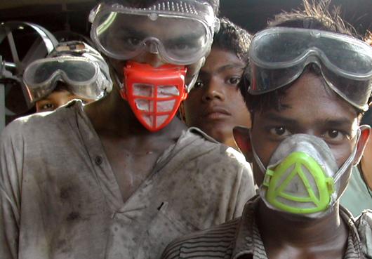 Alcuni giovani lavoratori del Bangladesh con mascherine e occhiali protettivi, con i vestiti sporchi dopo una giornata di lavoro.