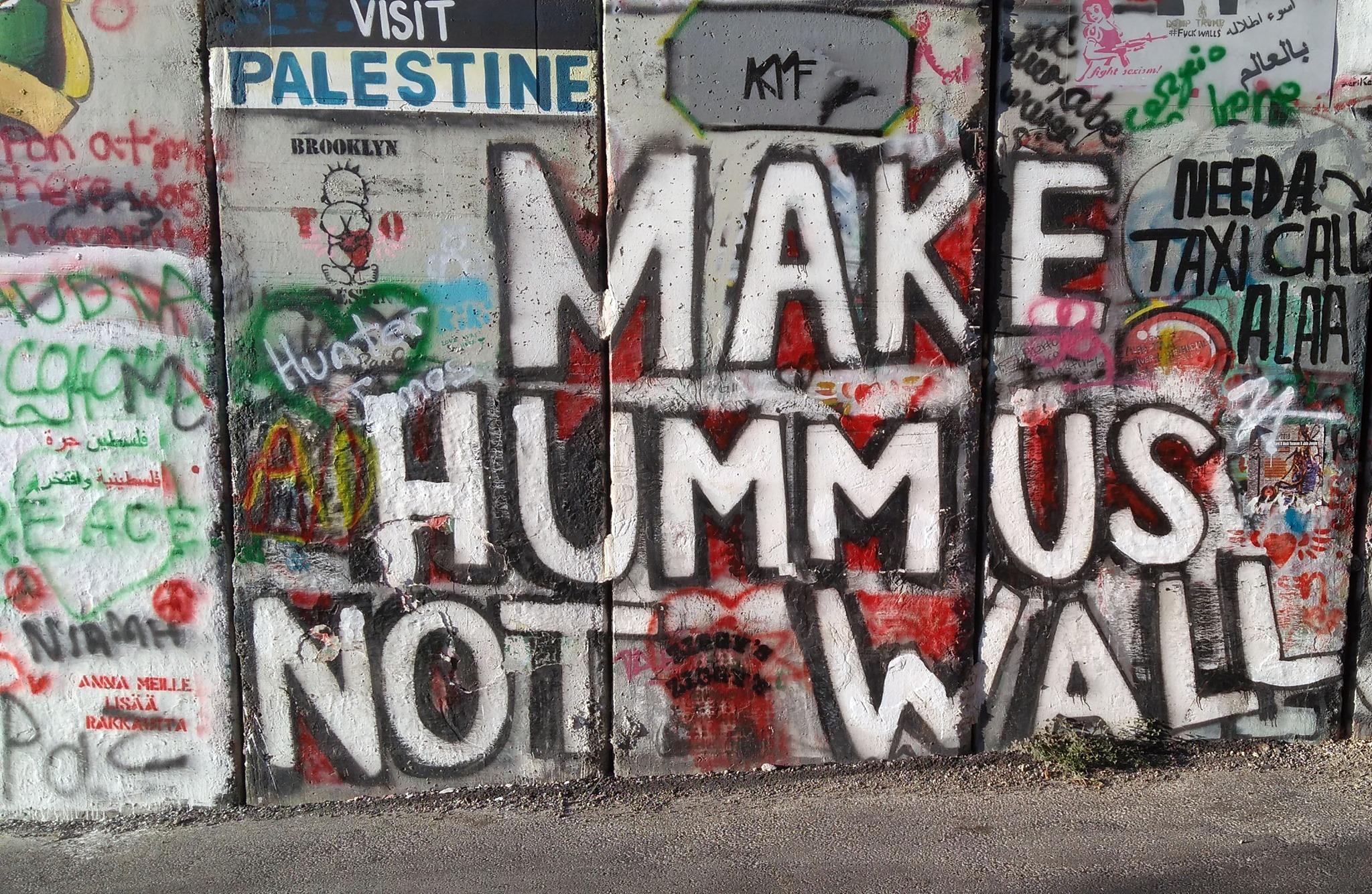"""Scritta """"Make hummus not wall"""" che si trova sul muro di divisione tra Israele e Palestina"""