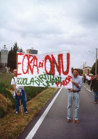 """Studenti della Scuola di Specializzazione in Istituzioni e Tecniche di tutela dei diritti umani portano uno striscione con la scritta """"E' ora di ONU""""  durante la Marcia per la Pace Perugia-Assisi, 1999."""