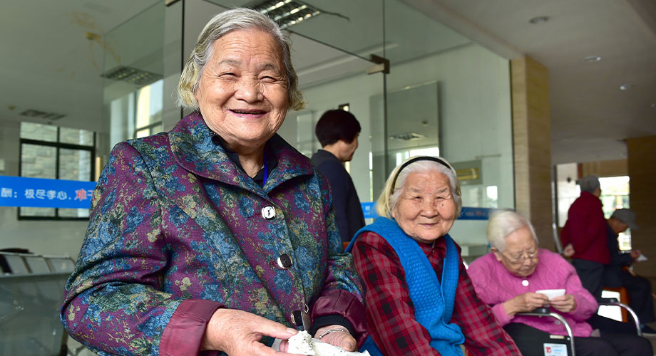 The image shows three old women in the waiting room of a hospital