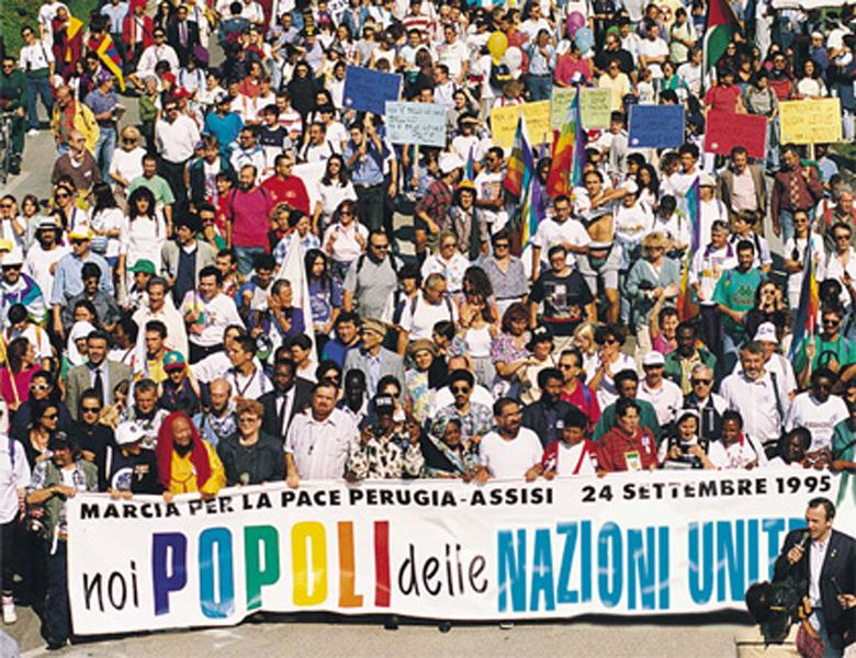 """Marcia per la Pace Perugia-Assisi, 24 settembre 1995. Una foto panoramica dell'inizio del corteo con lo stricione di apertura che recita """"Noi, popoli delle Nazioni Unite""""."""