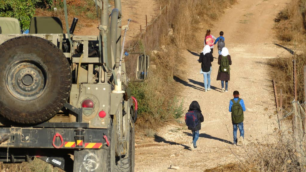 An Israeli military jeep escorting Palestinian schoolchildren to their school in Al-Tuwani in the West Bank, 2016.