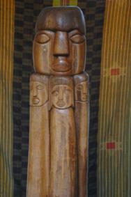 """Peace, opera dello scultore e poeta Gérard Voisin, proclamato """"Artista dell'UNESCO per la Pace"""", costituita da una colonna di legno intarsiata raffigurante volti di uomini stilizzati."""