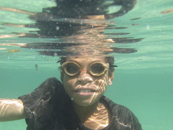 Un bambino che pesca con occhialini di legno nelle acque dell'isola di Atauro, Timor-Leste