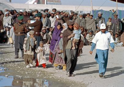 Un'intera famiglia afgana viene guidata dal personale del campo profughi Roghani a Chaman, al confine pakistano, nell'area a loro riservata