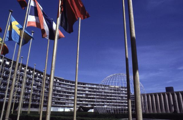 Facciata dell'edificio principale dell'UNESCO: in primo piano le bandiere degli Stati membri e il Globo, simbolo delle Nazioni Unite.