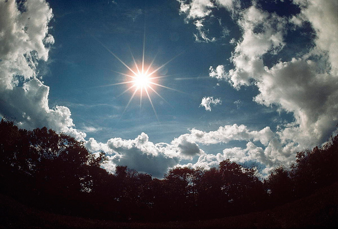 Sole che splende nel cielo azzurro con un contorno di nuvole bianche e in basso una cornice di alberi dalle foglie rosse