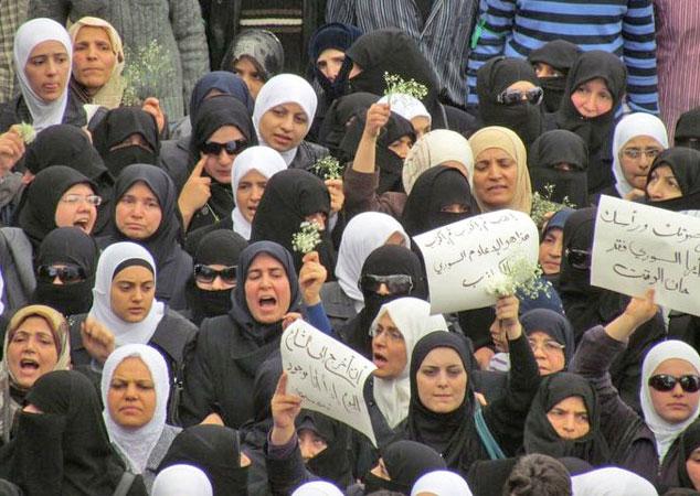 Un gruppo di donne siriane protesta mostrando dei cartelloni