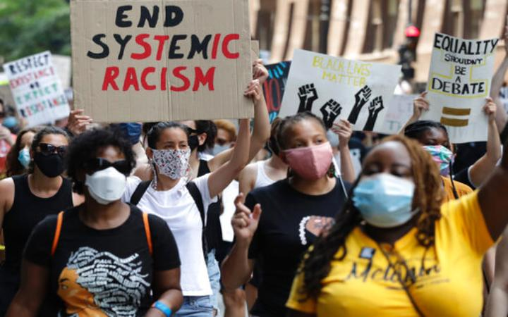 """protester hold sign saying """"end systemic racism"""""""