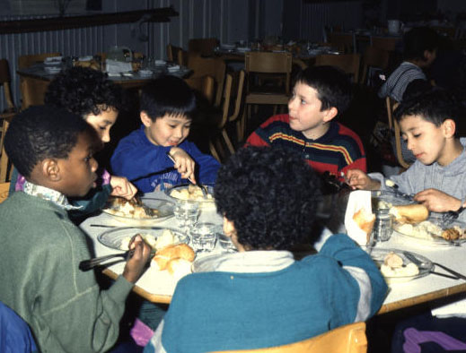 Bambini di diversa etnia mangiano insieme a tavola