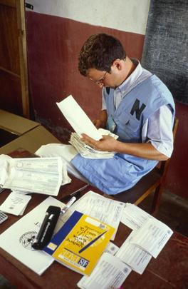 Un volontario ONU prepara le schede per il voto in un seggio elettorale in Timor Est  durante un'operazione di monitoraggio e assistenza elettorale.
