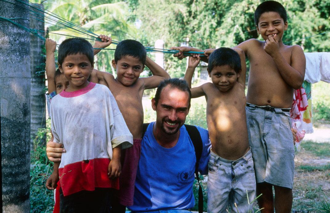 Un volontario a El Salvador mentre posa con bambini del posto, 1 gennaio 2001