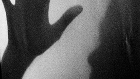 Photo on the subject of violence against women in East Timor. Black and white image of the faded silhouette and hand of a woman.