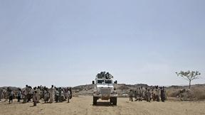 Una jeep bianca dei peacekeepers ONU transita tra due gruppi di persone a Kafod, Sudan
