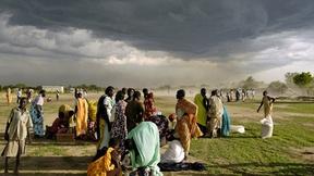Alcuni profughi raggruppati in un campo in Sudan ricevono razioni di cibo; sullo sfondo il cielo scuro preannuncia l'arrivo di una tempesta.