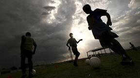 Haiti: foto controluce di alcuni ragazzi mentre giocano a calcio.