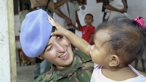 Una peacekeeper delle Nazioni Unite tiene in braccio una bambina che gioca, attirata dal suo cappello, Timor Est.