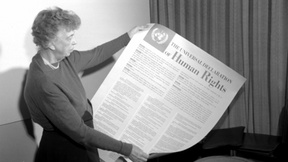 Black-and-white photo of Eleanor Roosevelt with a poster in hand, on which is written the text of the Universal Declaration of Human Rights.