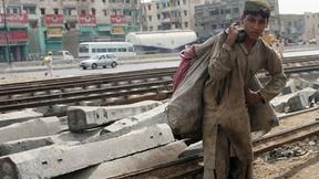 Ragazzo pakistano con umili vestiti mentre lavora in prossimità delle rotaie del treno a Karachi.