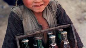 Primo piano di un bambino nepalese che vende delle bibite.