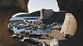 Scorcio di Dubrovnik attraverso un'apertura a forma di fiore, coinvolta nel conflitto dei Balcani.