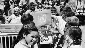 Gli osservatori ONU con la bandiera delle Nazioni Unite insieme ad un gruppo di bambini in Palestina, 1948.