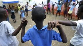 Bambini sfollati di haiti giocano insieme in un'area sicura predisposta dall'organizzazione internazionale Save the Children