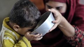 Una madre dà al proprio bambino una ciotola di acqua potabile nel distretto di Charsada,  nordest del Pakistan, 2010