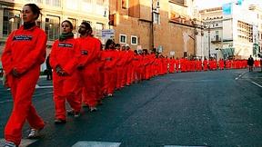 Una fila di persone sfila per la strada con le tute arancioni simili a quelle che indossano i detenuti a Guantanamo