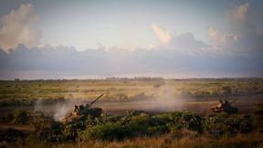 Due carrarmati somali, in collaborazione con la missione dell'Unione africana in Somalia, attraversano un campo al tramonto.