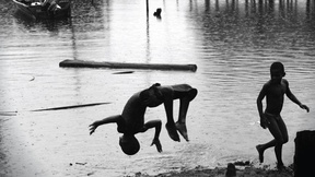 """fotografia in bianco e nero di bambini che giocano vicino ad una pozza d'acqua. In alto scritta """" 2015-2024 Decennio internazionale delle persone con origini africane. Riconoscimento giustizia e sviluppo"""" Logo delle nazioni unite e del decennio"""