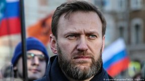Alexei Navalny's portrait during a manifestation and russian flag on the background
