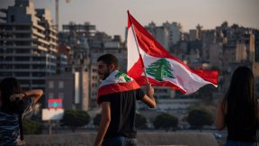 Man during Beirut protests with a flag from Lebanon