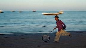 Immagine di un bambino che gioca con una ruota di bicicletta lungo la spiaggia in Iran