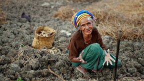 A woman seats on the ground of a bare land with her hands turned towards the observer
