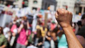 L'immagina mostra sullo sfondo un gruppo di persone che manifestano in strada e in primo piano un braccio con il pugno alzato.