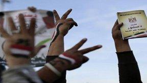 Manifestanti egiziani con la Costituzione in mano.