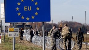 soldiers are closing the border with barbed wire, under an EU sign