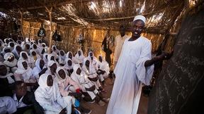 Un insegnante e i suoi studenti durante la lezione in aula nel campo per sfollati di Nifasha (Nord Darfur).