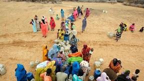 Gruppo di donne in abiti colorati al punto di distribuzione dell'acqua nel Nord Darfur. La fonte d'acqua più vicina si trova ad una distanza di un'ora e mezza; gli asini sono di solito usati per il trasporto dell'acqua al villaggio.