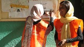 Due giovani donne dello staff elettorale stanno fissando con del nastro adesivo un cartello fuori dalla loro postazione elettorale a  Khartoum, Sudan, nel primo giorno delle elezioni nazionali.