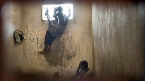 Nimba county prison inmate looks through a window of a cell, Liberia, 2008