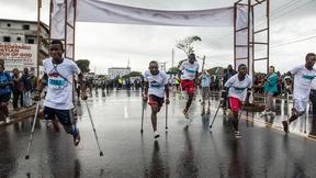 Atleti disabili si spingono in avanti alla partenza della Maratona in Liberia per persone con disabilità.