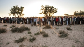 Centinaia di rifugiati libici in fila per il cibo al campo di transito vicino al confine tra Tunisia e Libia, 2011