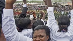 Una donna esulta durante la cerimonia per l'indipendenza del Sud Sudan, dietro di lei altre persone con le mani alzate e sullo sfondo le sfilate della cerimonia.